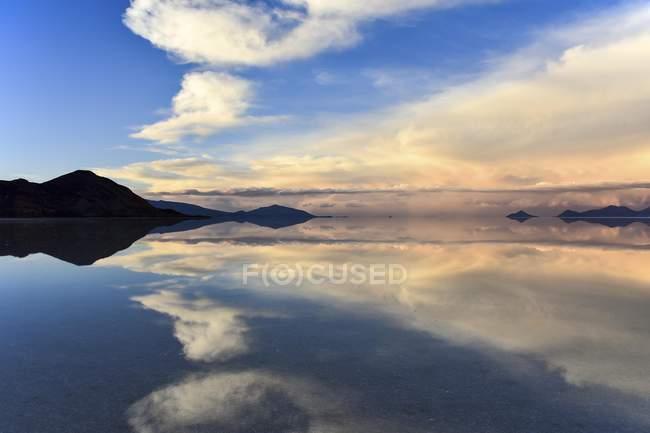 Bergen mit Reflexion in überfluteten Salzsee in der Abenddämmerung, Salar de Uyuni, Altiplano, Bolivien, Südamerika — Stockfoto