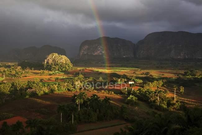 Campo de tabaco con paisaje de montaña karst con nubes de lluvia y arco iris en el valle de Viñales, Pinar del río, Cuba, Centro América - foto de stock
