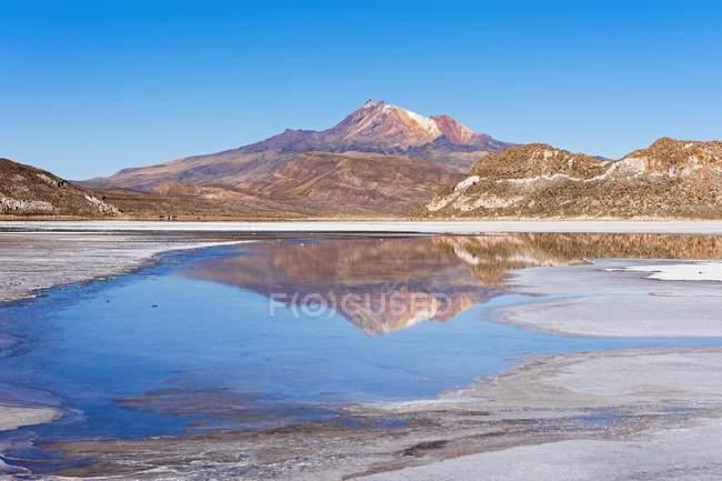 Volcano Cerro Tunupa with reflection in Salar de Uyuni salt lake, Altiplano, Bolivia, South America — Stock Photo