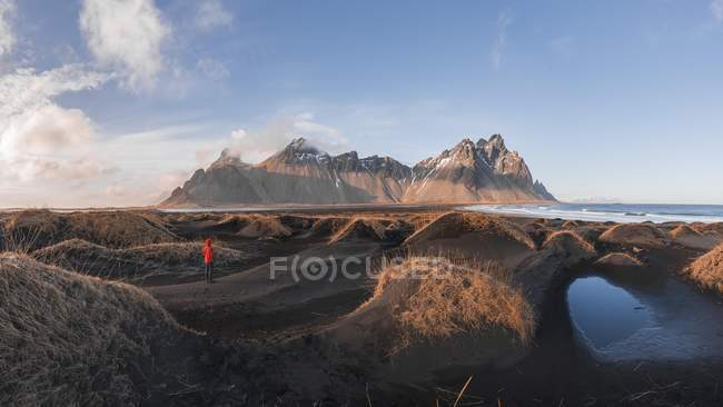 Ambiente en la playa de lava con viajero en negro las dunas de arena cubierto con hierba en la cordillera Klifatindur, Austurland, Islandia, Europa de noche - foto de stock