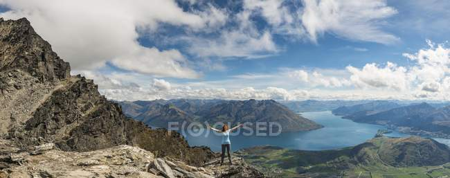 Female hiker standing with arms raised on Remarkables mountain range overlooking Lake Wakatipu, Queenstown, New Zealand — Stockfoto