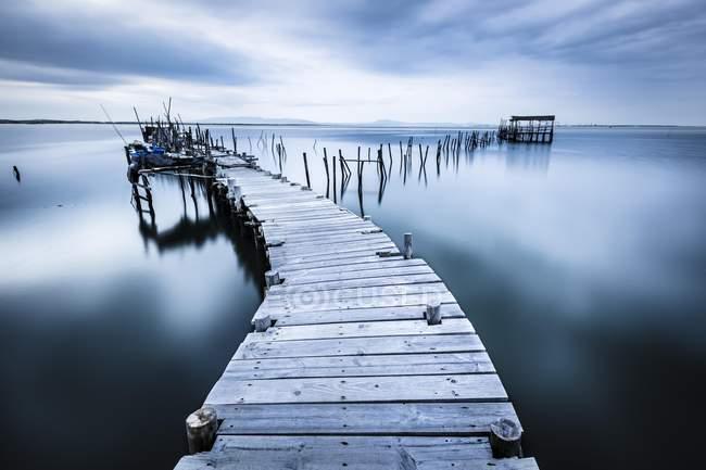 Embarcadero en la mar en calma en el humor de la noche, Carrasqueira, Alcacer sal, Portugal, Europa - foto de stock