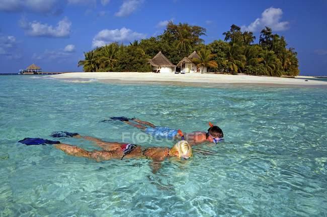 Praticantes de snorkel em águas rasas turquesa da ilha de Bathala, Maldivas, Ásia — Fotografia de Stock