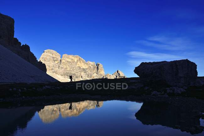 Lake water of Lavaredo mountain massif reflecting silhouette of hiker, Sexten Dolomites, South Tyrol, Italy, Europe — Stockfoto