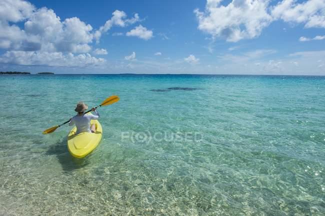 Жіночий туристичних каякінг у бірюзові води Tikehau, архіпелагу Туамоту, Сполучені Штати Америки, Океанії — стокове фото