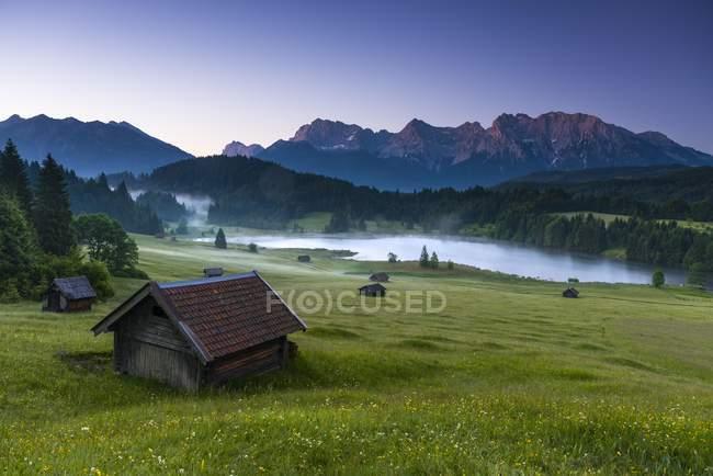 Kleine Hütten am Bergwiese am Waldrand, Geroldsee im Hintergrund Karwendelgebirge bei Sonnenaufgang, Kaltenbrunn, Oberbayern, Deutschland, Europa — Stockfoto