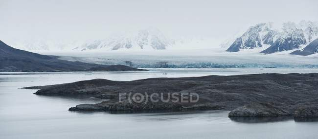 Headland with mountains and Monacobreen glacier in fog, Liefdefjorden fjord, Spitsbergen, Svalbard Islands, Svalbard and Jan Mayen, Norway, Europe — Stock Photo