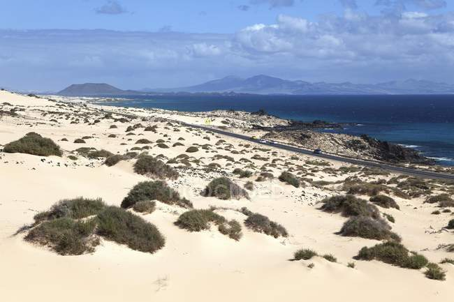 Road in wandering dunes El Jable, Corralejo Natural Park, with scenery of islands of Los Lobos and Lanzarote, Fuerteventura, Canary Islands, Spain, Europe — стоковое фото