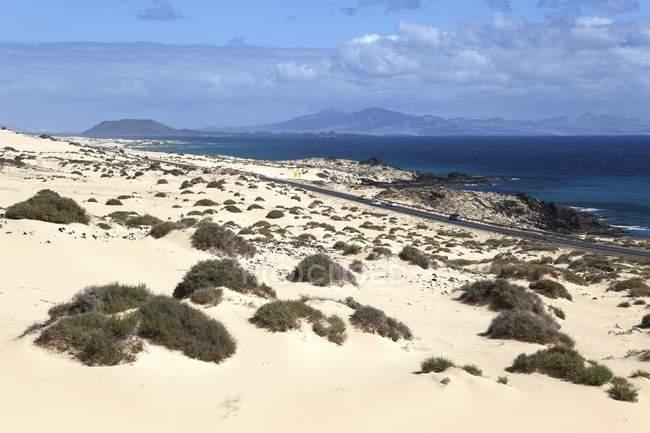 Route dans les dunes errantes El Jable, parc naturel de Corralejo, avec des paysages d'îles de Los Lobos et Lanzarote, Fuerteventura, Iles Canaries, Espagne, Europe — Photo de stock