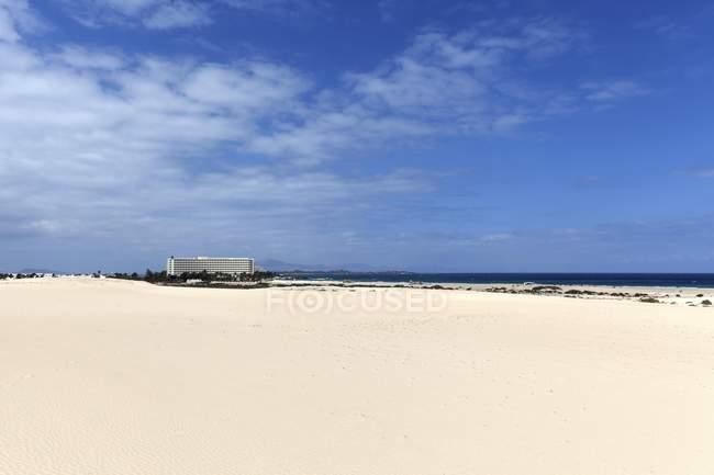 Dunes de sable blanc et bâtiment d'hôtel dans les dunes errantes d'El Jable, Las Dunas de Corralejo, parc naturel de Corralejo, Fuerteventura, Iles Canaries, Espagne, Europe — Photo de stock