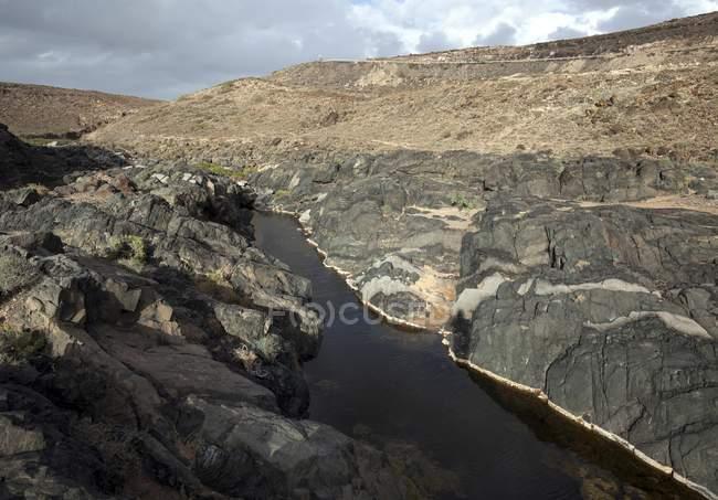 River in rocky Barranco de los Molinos, Los Molinos, Fuerteventura, Canary Islands, Spain, Europe — стоковое фото