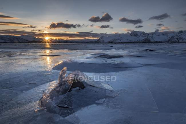 Broken ice of frozen fjord with mountains at sunset with solar reflection, Gimsoy, Lofoten, Norway, Europe — Stock Photo