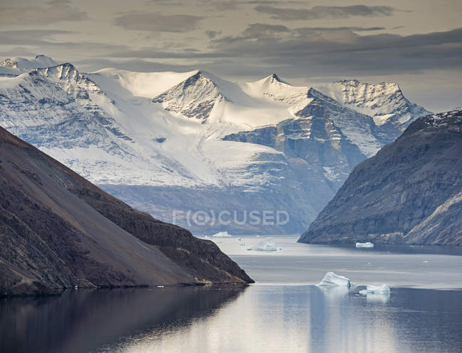 Mountain slopes and snowy mountains with icebergs in Blomsterbugten, Kejser Franz Joseph Fjord, Northeast Greenland National Park, Greenland, North America — Stock Photo