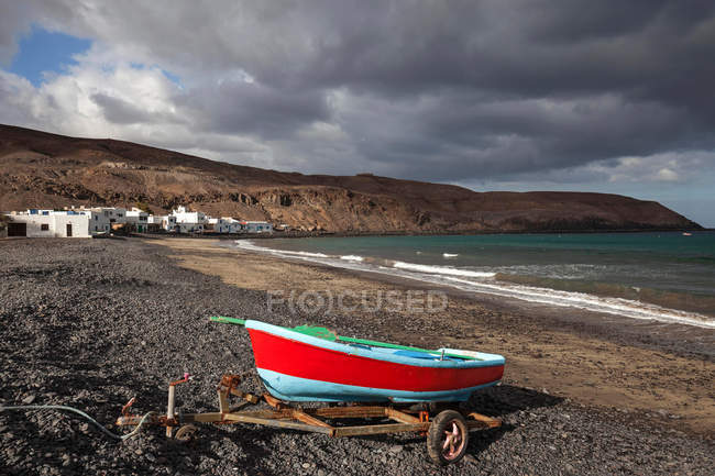 Small colorful fishing boat on beach of fishing village Pozo Negro under dark clouds, Fuerteventura, Canary Islands, Spain, Europe — стоковое фото