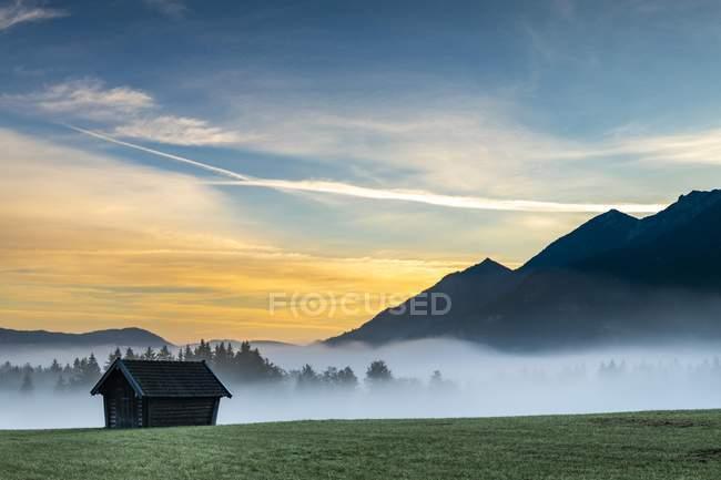Wiese Berghütte mit Bodennebel und Karwendelgebirge im Hintergrund mit Sonnenaufgang, Krun, Bayern, Deutschland, Europa — Stockfoto