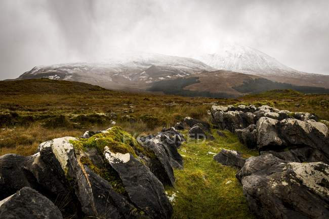 Dark rocks with white caps in Highlands landscape with snow-covered Cullin mountains, Broadford, Isle of Skye, Scotland, United Kingdom, Europe — Photo de stock