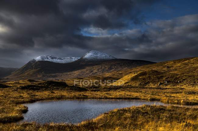 Small lake and snow-covered mountain peaks of Meall aBhiridh and Clach Leathad under dramatic clouds, Glen Coe, Rannoch Moor, west Highlands, Scotland, United Kingdom, Europe — Stock Photo