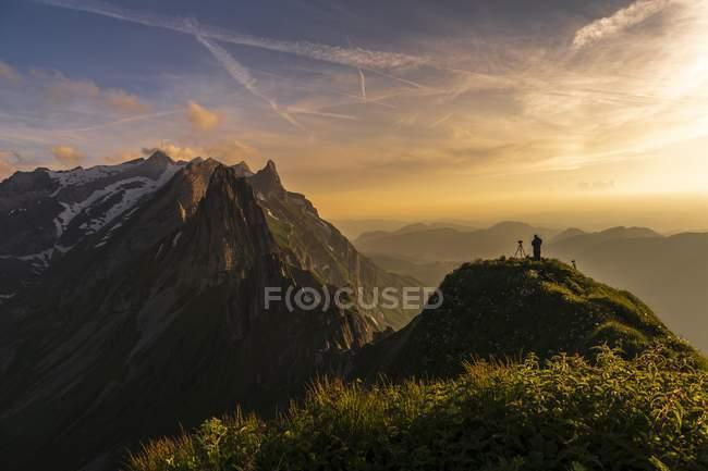 Фотограф на травянистых хребта на закате с Сантис пики в Европе Аппенцелль, Швейцария, фон, Wasserauen, — стоковое фото