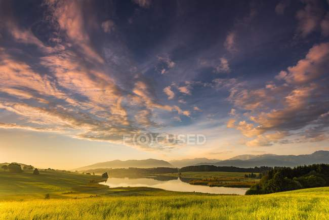 Forggensee lake with reflection of cloudy sky and Allgau mountains at sunrise, Fussen, Allgau, Bavaria, Germany, Europe — Stock Photo