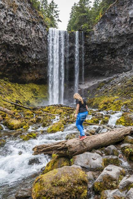 Young woman crossing river, Tamanawas Falls, wild river Cold Spring Creek, Oregon, USA, North America — Stockfoto