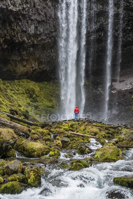 Hiker in front of waterfall over rocky outcrop, Tamanawas Falls, Cold Spring Creek, Oregon, USA, North America — Stockfoto
