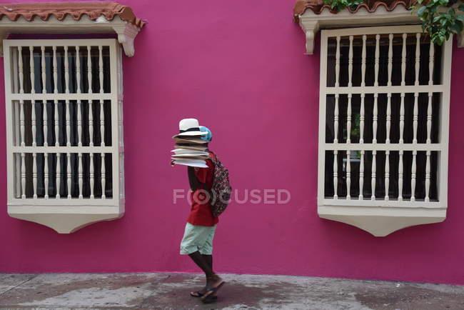 Продавець прогулянки з капелюхи, рожева будівля — стокове фото