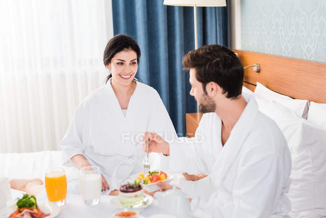 Selective focus of happy woman looking at bearded man holding fork near fruit salad — Stock Photo