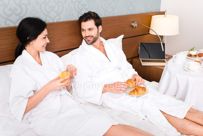 Cheerful man holding croissants while looking at woman with glass of orange juice — Stock Photo