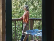 Donna in piedi sul balcone baita — Foto stock