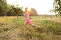 Mulher de vestido rosa correndo em campo — Fotografia de Stock