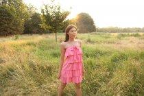 Jovem mulher de vestido em pé no campo — Fotografia de Stock