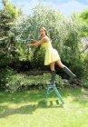 Donna in vestito giallo guarnizione albero — Foto stock