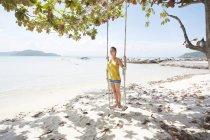 Donna in piedi su altalena in spiaggia — Foto stock