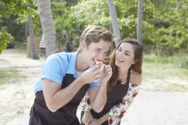 Man eating on beach with woman — Stock Photo