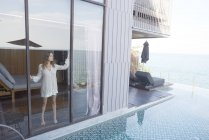 Woman standing by poolside window — Stock Photo