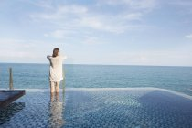 Woman in swimming pool looking at seascape — Stock Photo