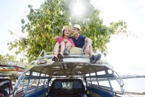 Pareja sentada en el techo de autobús tour - foto de stock