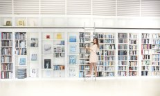 Woman standing on ladder in library — Stock Photo