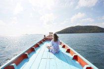 Donna che si siede sulla barca blu — Foto stock