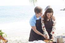 Casal de preparo de alimentos na praia — Fotografia de Stock