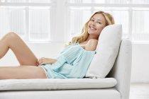 Жінка, лежачи на дивані і посміхається на камеру — стокове фото