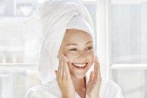 Mulher aplicando hidratante no rosto — Fotografia de Stock