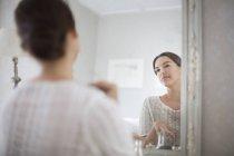 Жінка дивиться на себе у дзеркалі — стокове фото