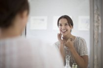 Woman looking at herself in mirror — Stock Photo