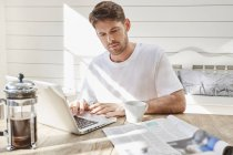 Man using laptop and looking at newspaper — Stock Photo