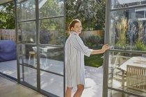 Mulher de pé na porta aberta — Fotografia de Stock