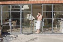 Hombre beber café por puerta abierta - foto de stock