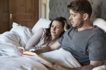 Couple reading in bed together — Stock Photo