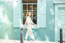 Woman walking along sidewalk — Stock Photo