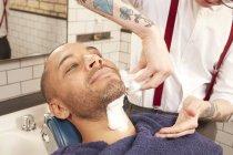 Barber shaving mid adult man — Stock Photo
